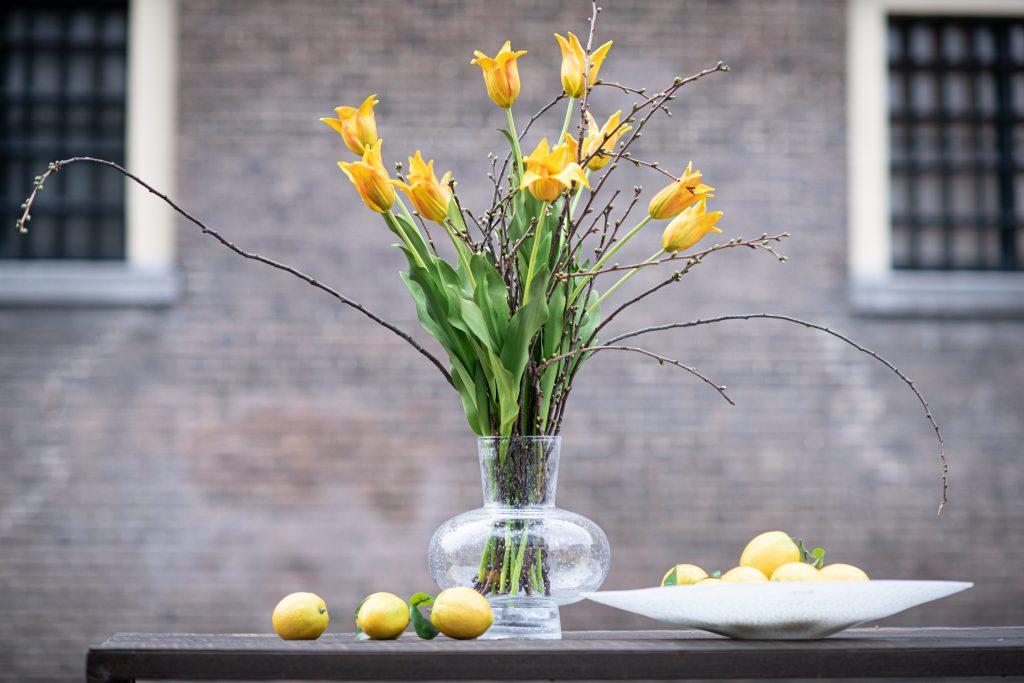 Modest vase in klar glas und weisse platte mit zitronen