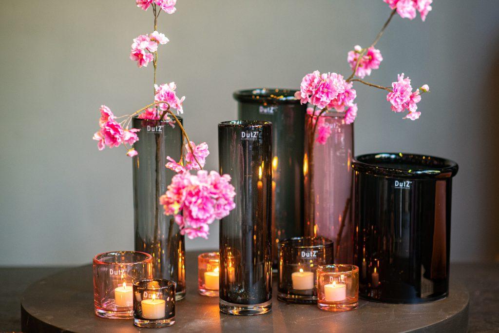 Graue und rosa zylinder und kerzenhalter auf ein runde tisch