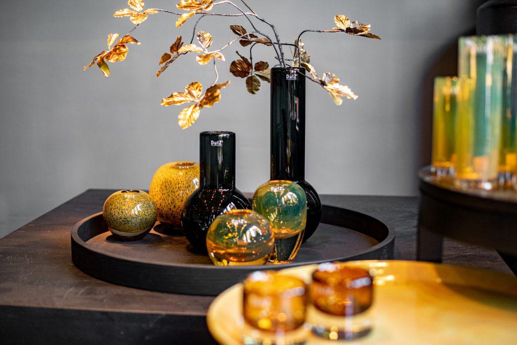 Meryna vase in grau und gold topaz ball vasen und Holla vasen in gold auf ein runde platte