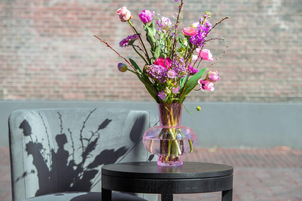 Modest vase in die Farbe aprikose mit viel blumen. Steht auf ein Tisch