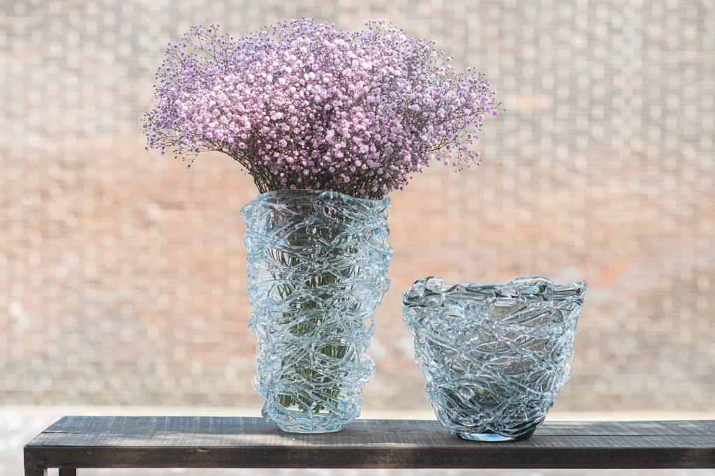 Nest Vase grau einmal klein und einmal gross. In die grosse stehen Blumen