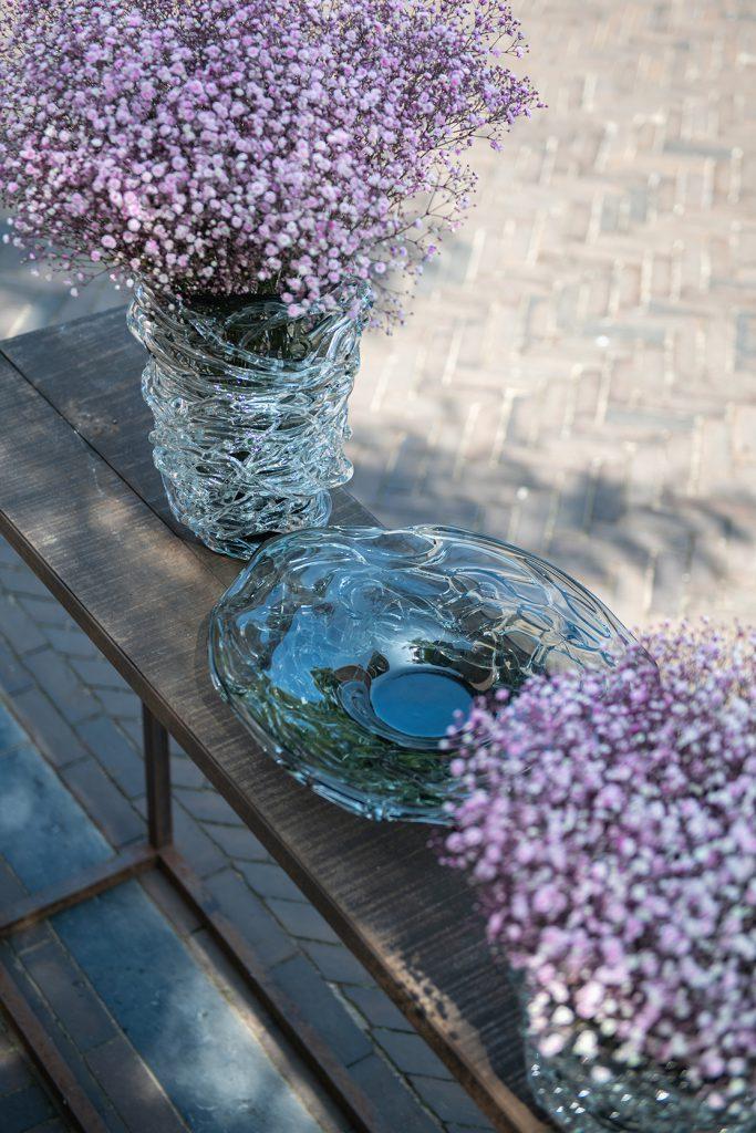 Vase und platte Nest. In Vase Nest stehen blumen