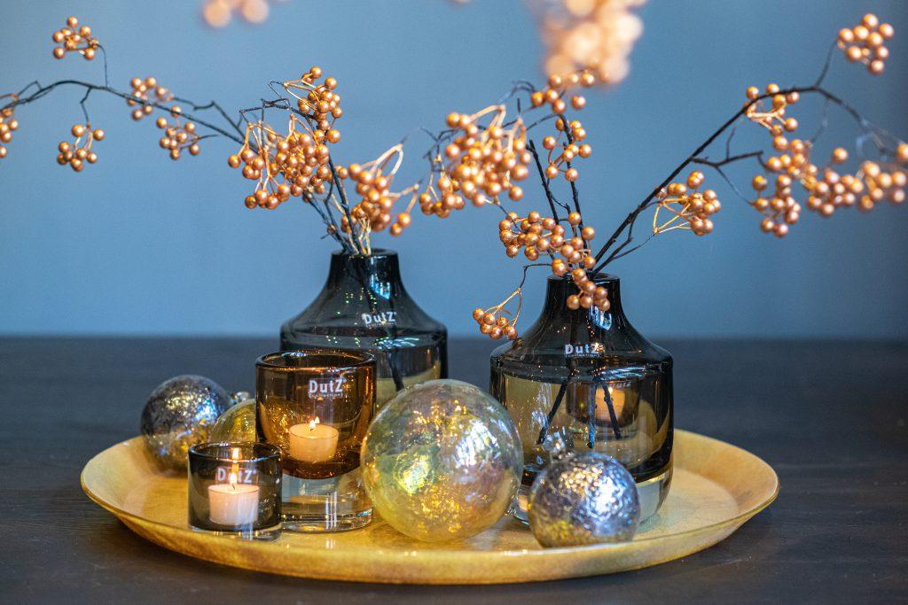 Graue Novak vasen und deco kugeln in gold farben auf ein goldfarbige glassplatte